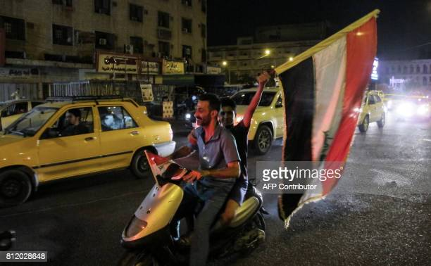 TOPSHOT An Iraqi waves a national flag as he rides in the back of a scooter with another while celebrating at the Tahrir Square in the capital...