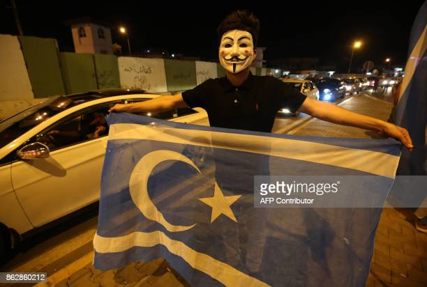 An Iraqi waves the flag of the Iraqi Turkmen people as he walks in the street in the city of Kirkuk to celebrate on October 18 after Iraqi government...