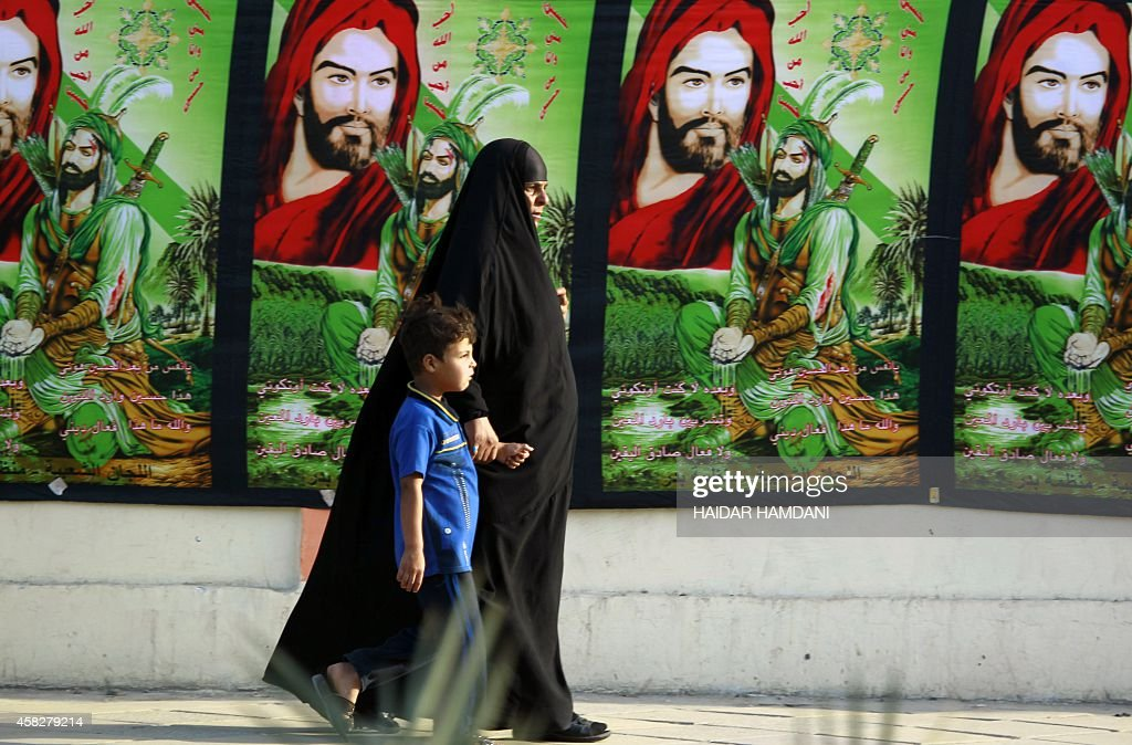 An Iraqi woman and boy walk in front of posters bearing the image of Imam Hussein one of Shiite Islam's most revered figures on the eve of the peak...