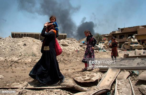 TOPSHOT An Iraqi woman and children flee the Old City of Mosul on July 3 during the government forces' ongoing offensive to retake the city from...