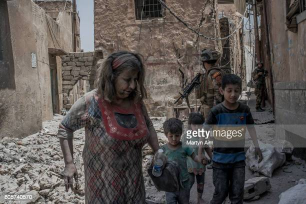 An Iraqi woman and her children flee the Old City district where heavy fighting continues on July 2 2017 in Mosul Iraq Iraqi forces continue to...
