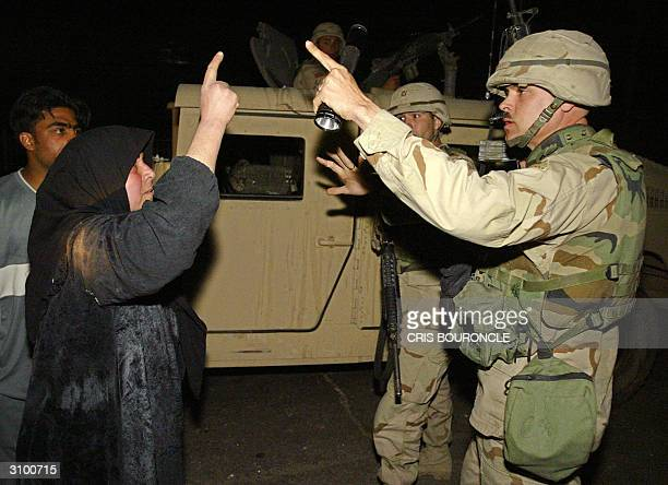 An Iraqi woman argues with US soldiers at the scene of an explosion which killed late16 March 2004 an Iraqi civilian and wounded five others as...