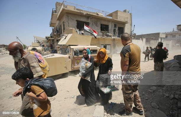 TOPSHOT An Iraqi woman carries a birdcage as she flees with other civilians from the Old City of Mosul as Iraqi forces advance on June 20 during the...