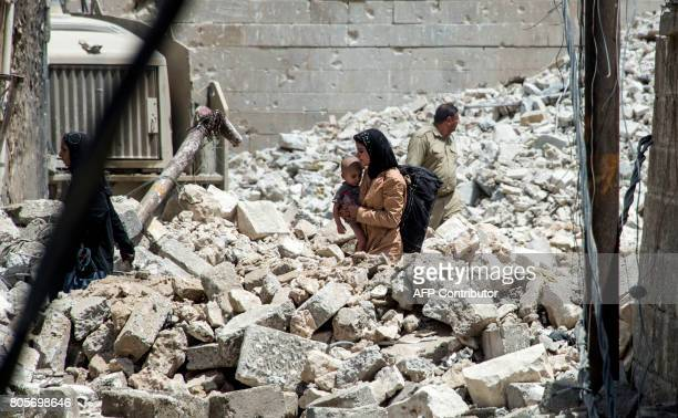 TOPSHOT An Iraqi woman carries a child as she walks through the rubble in the Old City of Mosul on July 2 during the offensive to retake the city...