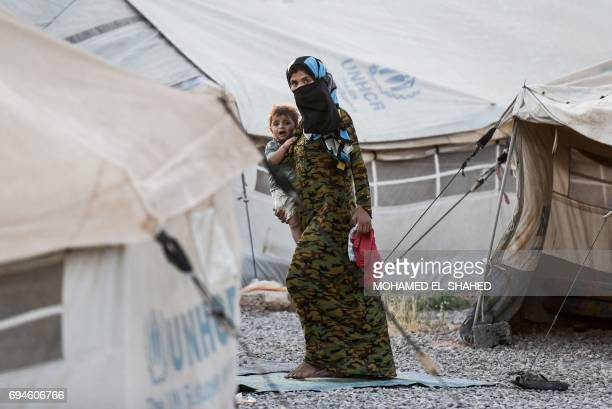 An Iraqi woman carries a child at the Hasan Sham camp for internally displaced people on June 10 2017 Tired and traumatised Iraqi mothers who fled...