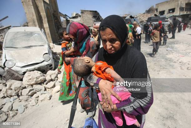 An Iraqi woman carries an child while walking by the destroyed AlNuri Mosque as she flees from the Old City of Mosul on July 5 during the Iraqi...