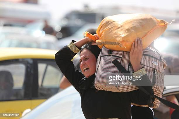 An Iraqi woman carries her property while fleeing from Mosul to Arbil and Duhok due to the clashes between security forces and militants of Islamic...