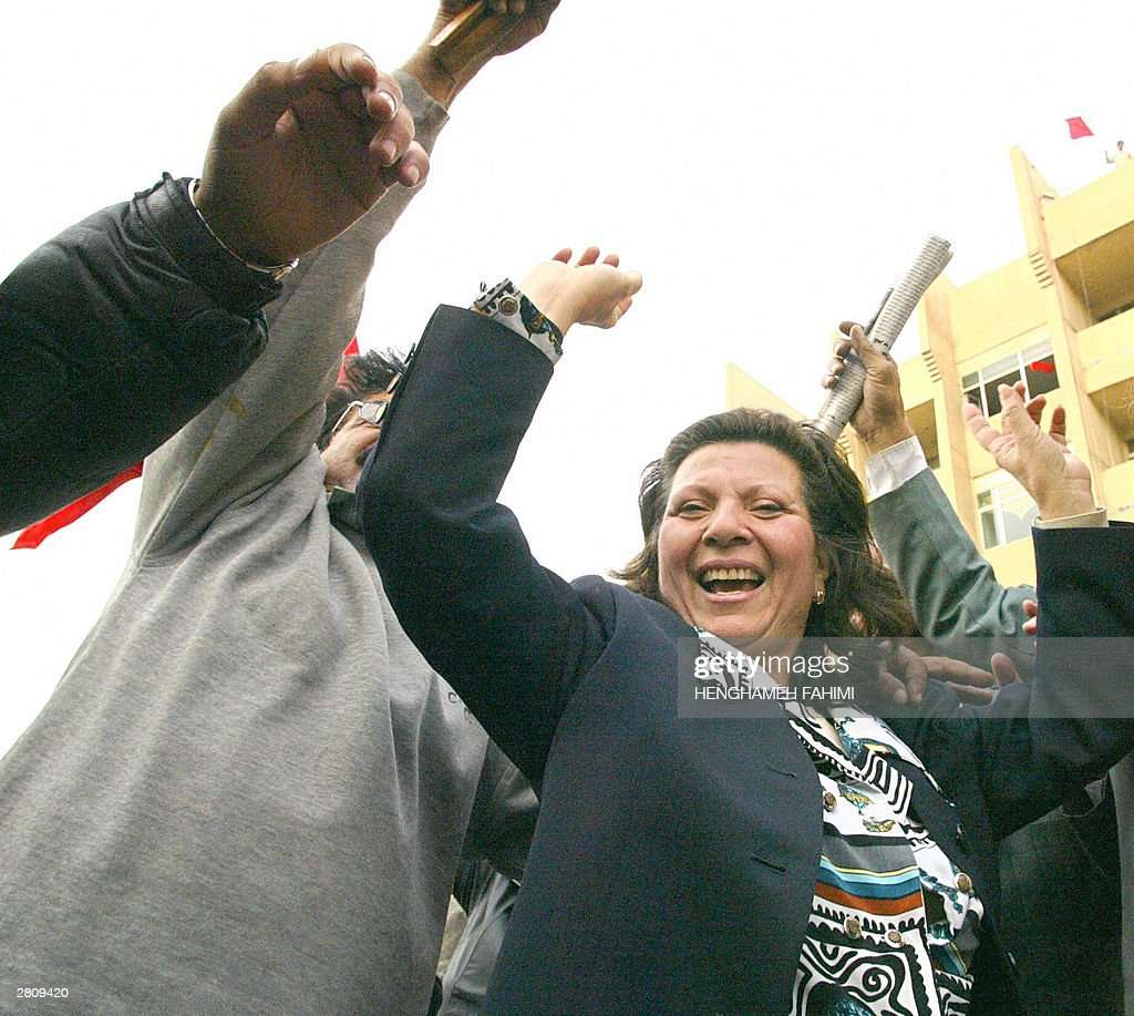 An Iraqi woman celebrates the capture of ousted ictator Saddam Hussein 14 December 2003 in front of Communist party headquarters in Baghdad. Saddam Hussein has been captured alive by coalition forces after a manhunt of more than eight months, US civil administrator Paul Bremer said said at a press conference, which he began with the dramatic announcement, 'Ladies and gentlemen, we got him.' Saddam, 66, was seized late 13 December in a raid near his hometown of Tikrit, north of the capital. AFP PHOTO/Henghameh FAHIMI