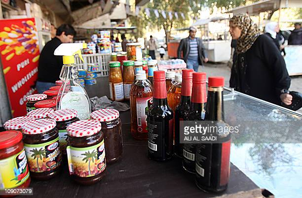 An Iraqi woman checks the prices of jam and concentrated drinks at one of the stalls in central Baghdad's outdoor market on February 10 2011 The...