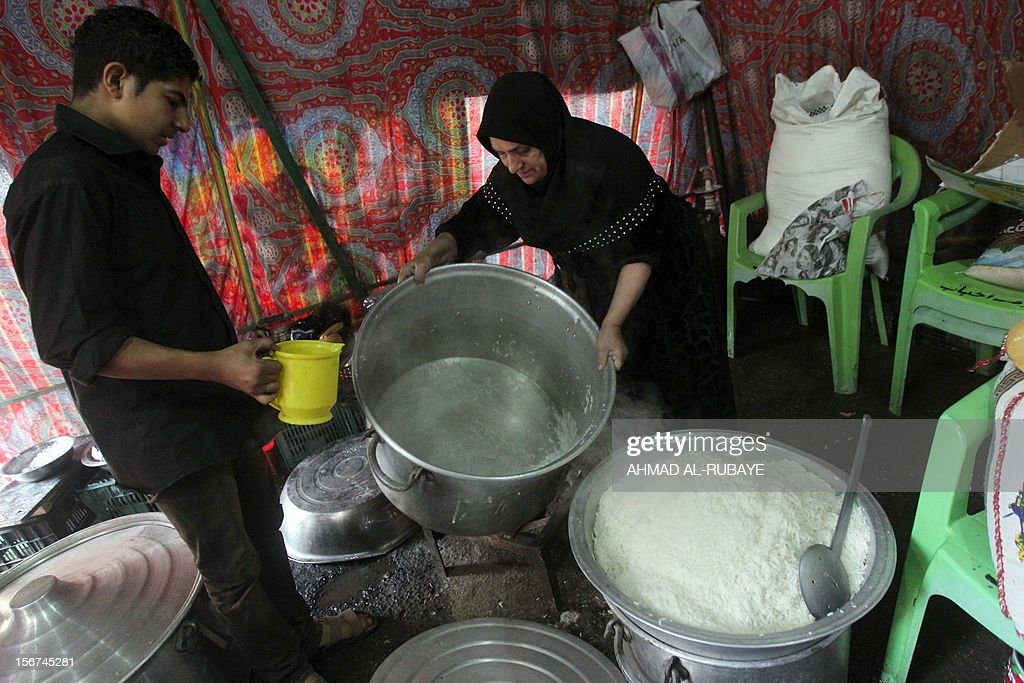 An Iraqi woman cooks a huge pot of rice for Muslim Shiite pilgrims as believers begin to gather for the upcoming Ashura rituals in Baghdad, on November 20, 2012. Ashura mourns the death of Imam Hussein, a grandson of the Prophet Mohammed, who was killed by armies of the caliph Yazid near Karbala in 680 AD. AFP PHOTO/AHMAD AL-RUBAYE