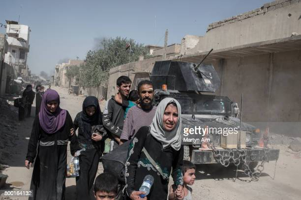 An Iraqi woman cries as she arrives safely with her family to an Iraqi Army position after fleeing the Islamic State controlled Old City of west...