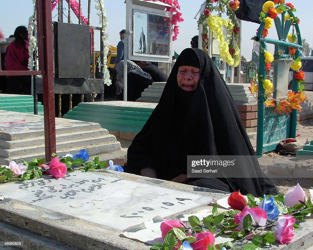 An Iraqi woman cries as she visits her relative's grave at the Najaf cemetery in the first day of Eid al-Fitr holiday on November 3, 2005 in the holy Shiite city of Najaf, Iraq.