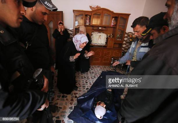 An Iraqi woman cries over her son's body who was killed by a mortar shell fired by Islamic State group jihadists on civilians who were gathered to...