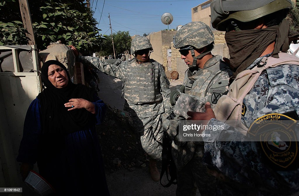 An Iraqi woman (L) discusses the state of her neighborhood with Staff Sgt. Mario Garcia (R, center) with the 2nd Battalion, 30th Infantry Regiment along with a translator (R,left) and an Iraqi National Police member (far L) during morning foot patrol in the Baladiyat neighborhood May 15, 2008 in Baghdad, Iraq. 10th Mountain Division soldiers in the area take daily joint patrols with the Iraqi National Police, in the ongoing effort to build up stable national Iraqi security institutions aligned with the national government.