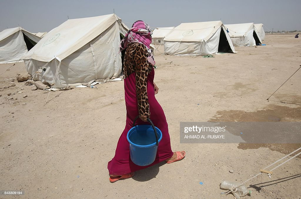 An Iraqi woman displaced from the city of Fallujah carries a bucket of water at a newly opened camp where hundreds of displaced Iraqis are taking shelter in Amriyat al-Fallujah on June 27, 2016, south of Fallujah. Iraqi forces on June 26 wrapped up operations in Fallujah and declared the area free of jihadists from the Islamic State (IS) group after a month-long operation. The government said the destruction caused by the fighting was limited and vowed to do its utmost to allow the tens of thousands of displaced civilians to return to their homes. RUBAYE