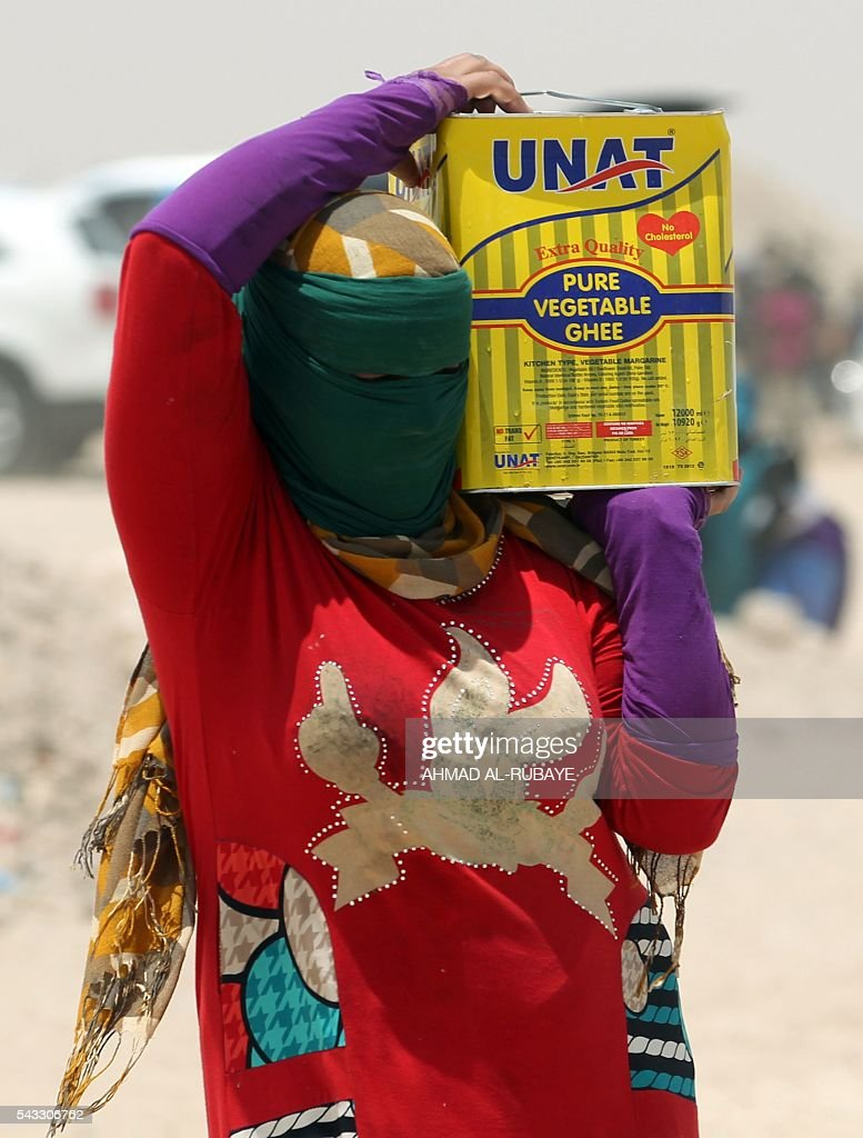 An Iraqi woman displaced from the city of Fallujah carries a can of oil distributed by the Norwegian Refugee Council at a newly opened camp where hundreds of displaced Iraqi are taking shelter in Amriyat al-Fallujah on June 27, 2016, south of Fallujah. Iraqi forces on June 26 wrapped up operations in Fallujah and declared the area free of jihadists from the Islamic State (IS) group after a month-long operation. The government said the destruction caused by the fighting was limited and vowed to do its utmost to allow the tens of thousands of displaced civilians to return to their homes. RUBAYE