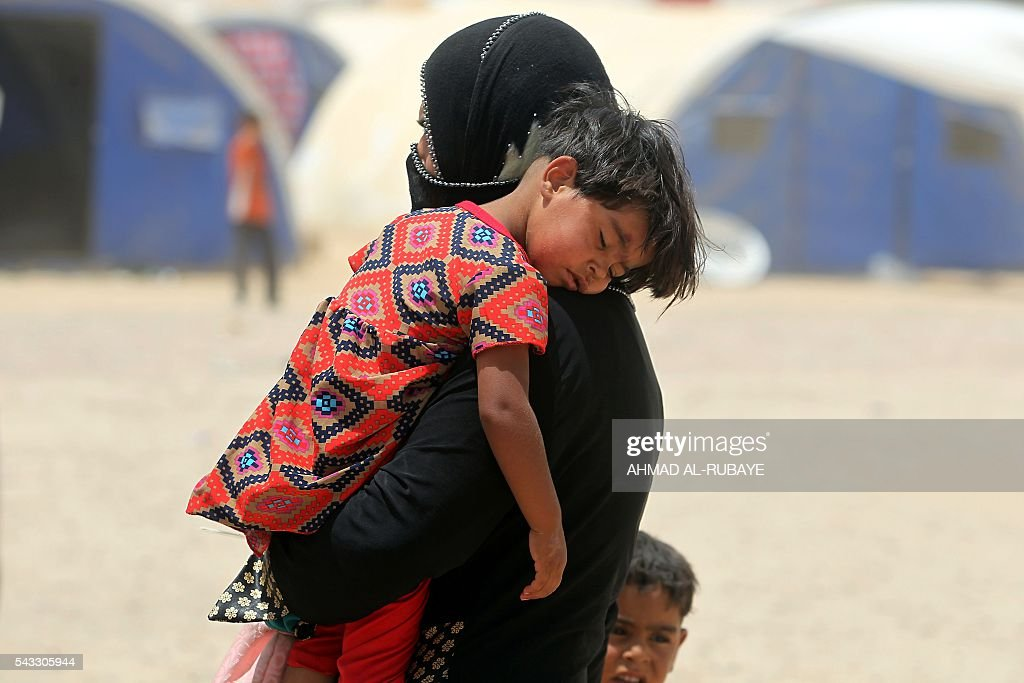 An Iraqi woman displaced from the city of Fallujah carries a child at a newly opened camp where hundreds of displaced Iraqis are taking shelter in Amriyat al-Fallujah on June 27, 2016, south of Fallujah. Iraqi forces on June 26 wrapped up operations in Fallujah and declared the area free of jihadists from the Islamic State (IS) group after a month-long operation. The government said the destruction caused by the fighting was limited and vowed to do its utmost to allow the tens of thousands of displaced civilians to return to their homes. RUBAYE