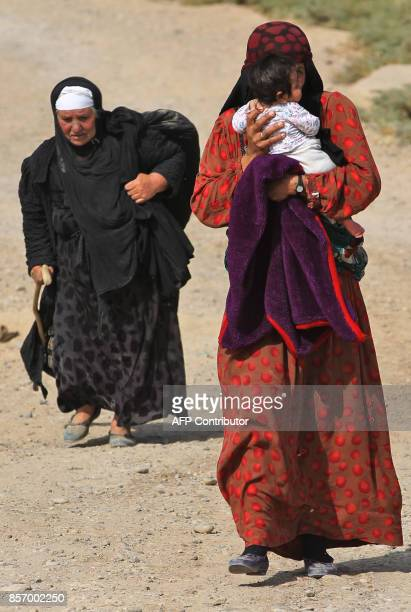 An Iraqi woman displaced from the outskirts of Islamic State group stronghold Hawija carries a child while travelling with family members and a...