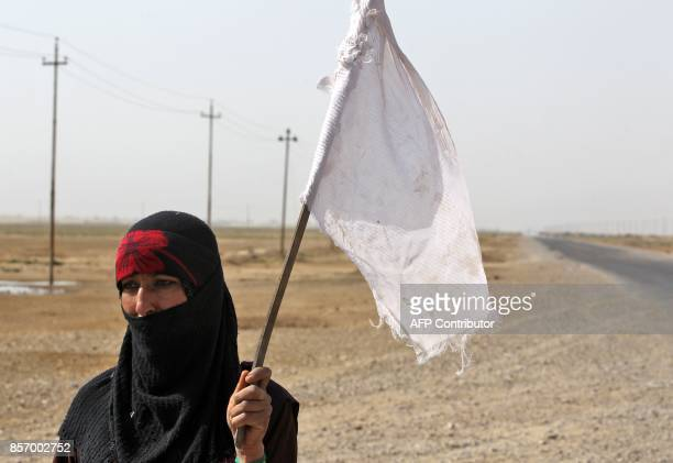 An Iraqi woman displaced from the outskirts of Islamic State group stronghold Hawija raises a white flag while travelling with family members and a...