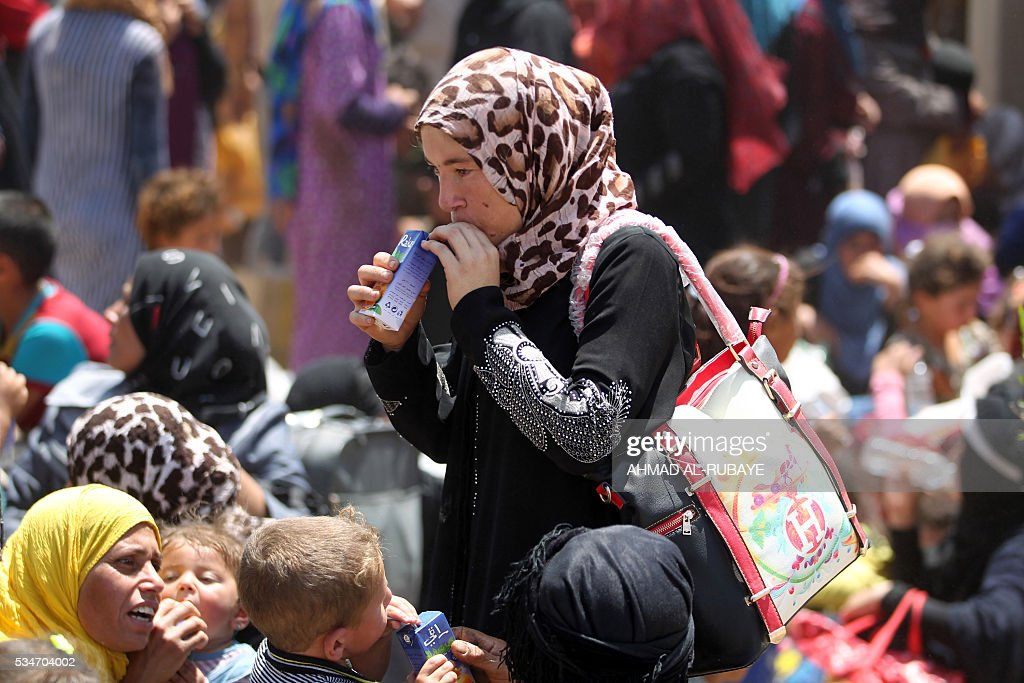An Iraqi woman drinks juice are pictured near al-Sejar village, in Iraq's Anbar province, after fleeing the city of Fallujah, on May 27, 2016, during a major operation by Pro-government forces to retake the city of Fallujah, from the Islamic State (IS) group. Hundreds of people fled the Fallujah area with the help of Iraqi forces, officials said. / AFP / AHMAD