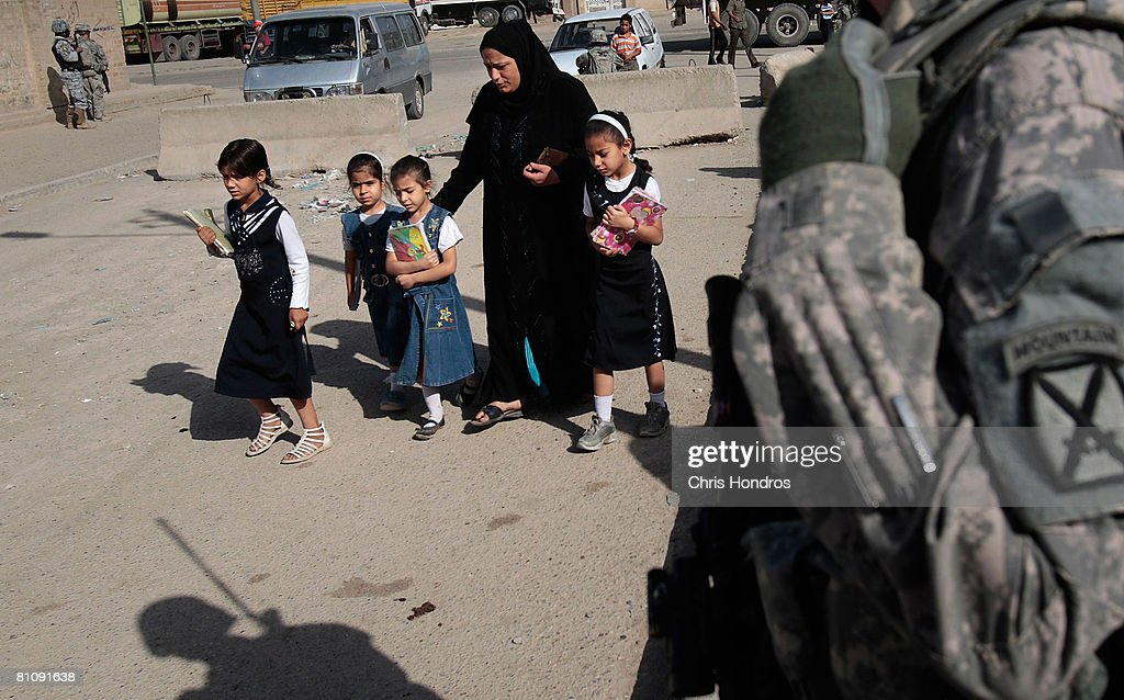 An Iraqi woman escorts girls to school past a US Army soldier during a morning patrol in the Baladiyat neighborhood May 15, 2008 in Baghdad, Iraq. 10th Mountain Division soldiers in the area take daily joint patrols with the Iraqi National Police, in the ongoing effort to build up stable national Iraqi security institutions aligned with the national government.