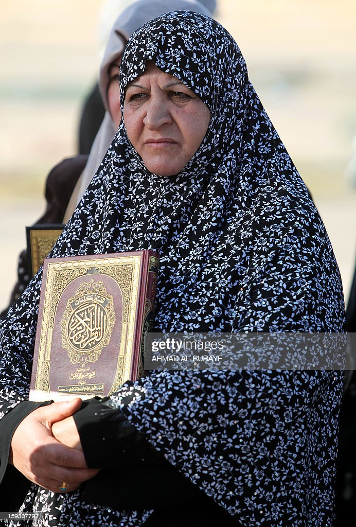 An Iraqi woman holds a copy of the Koran, Islam's holy book, during an anti-government protest outside the Sunni Umm al-Qura mosque in Baghdad on January 11, 2013. Thousands of Sunni Muslims took to the streets of Baghdad and other parts of Iraq to decry the alleged targeting of their minority, in rallies hardening opposition to the country's Shiite leader. AFP PHOTO/AHMAD AL-RUBAYE