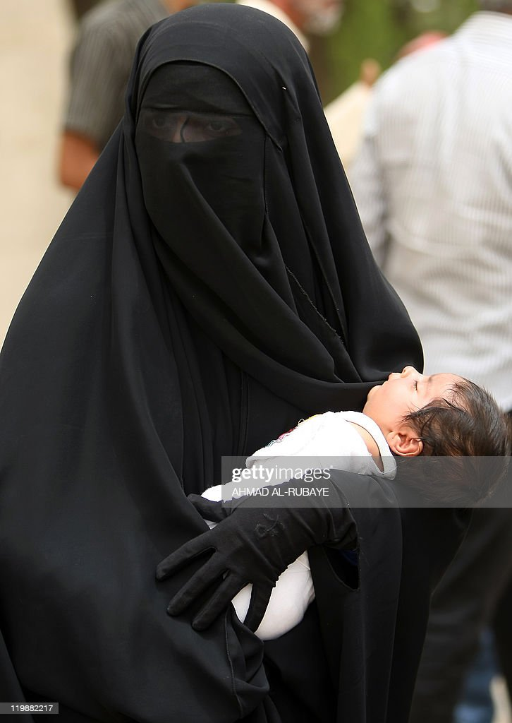 An Iraqi woman holds her baby as she takes part in a protest calling for the pardon or retrial of prisoners who demonstrators say were sentenced...