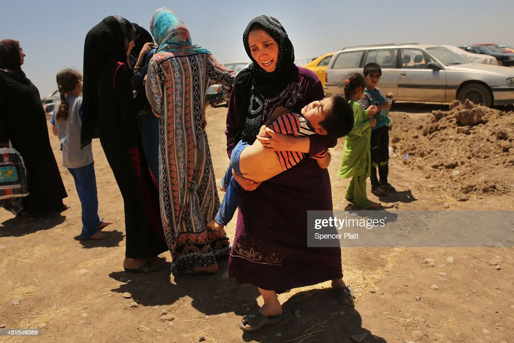 An Iraqi woman holds her exhausted son as over 1000 Iraqis who have fled fighting in and around the city of Mosul and Tal Afar wait at a Kurdish checkpoint in the hopes of entering a temporary displacement camp on July 1, 2014 in Khazair, Iraq. The families, many with small and sick children, had no shelter and little water and food. The displacement camp Khazair is now home to an estimated 1,500 internally displaced persons (IDP's) with the number rising daily. Tens of thousands of people have fled Iraq's second largest city of Mosul after it was overrun by ISIS (Islamic State of Iraq and Syria) militants. Many have been temporarily housed at various IDP camps around the region including the area close to Erbil, as they hope to enter the safety of the nearby Kurdish region.