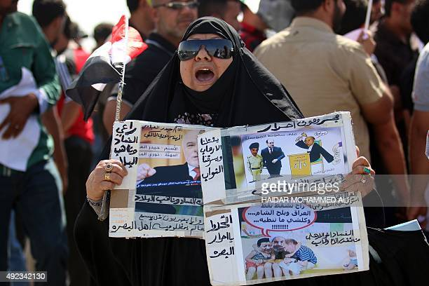 An Iraqi woman holds placards with antigovernment slogans accusing politicians of corruption as Iraqi merchants from the Basra region demonstrate...