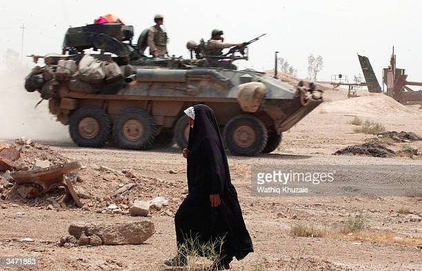 An Iraqi woman ia passed by an US Army Stryker Armored vehicle as she leaves April 27 2004 in Fallujah Iraq US Marines and Iraqi security personnel...
