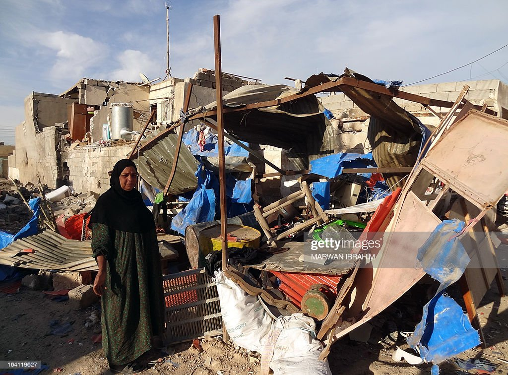 An Iraqi woman inspects the damage following a car bomb attack that happened late at night in Kirkuk, 240 kilometers north of Baghdad, on March 20, 2013, that killed one and wounded several. Kirkuk, an ethnically mixed city lies at the heart of a swathe of disputed territory claimed by both the central government and Iraq's autonomous northern Kurdish region.