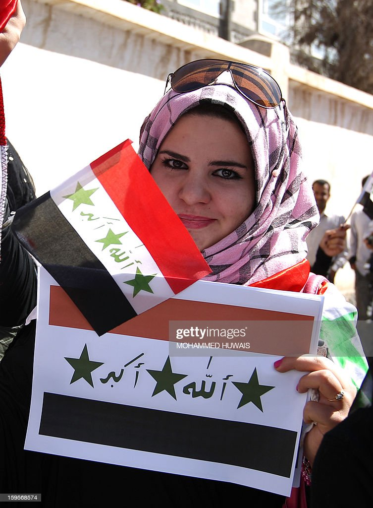 An Iraqi woman living in Yemen holds-up the Iraqi flag used during the Baath Party's rule under ousted Iraqi leader Saddam Hussein, as they take part in a protest in front of the Iraqi Embassy, in the capital Sanaa on January 16, 2013, demanding the sacking of Iraqi Prime Minister Nuri al-Maliki. Iraq is engulfed in a political crisis with Prime Minister Maliki facing several protests hardening opposition against his rule and calls for his ouster from many of his erstwhile government partners. AFP PHOTO/ MOHAMMED HUWAIS