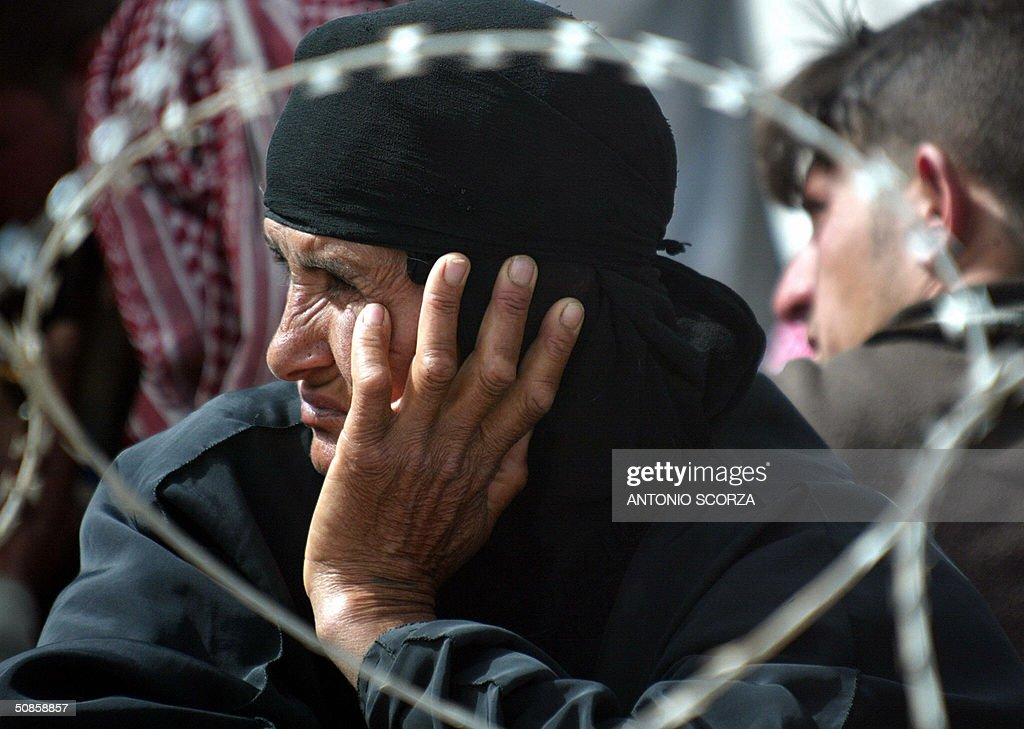 An Iraqi woman looks on as she waits at the entrance of the Abu Ghraib prison 20 May 2004 in hope of getting information about a relative held by US forces at the detention center, 30 kms west of Baghdad. US troops faced further embarrassment amid claims they killed dozens of people at a wedding celebration in a remote western Iraqi town, at a time when the occupation forces are already reeling from a prison abuse scandal. AFP PHOTO/Antonio SCORZA