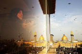 An Iraqi woman prays on March 18 2006 as Imam Abbas mosque is seen in the holy Shiite city of Karbala south of Baghdad Iraq Tens of thousands of...