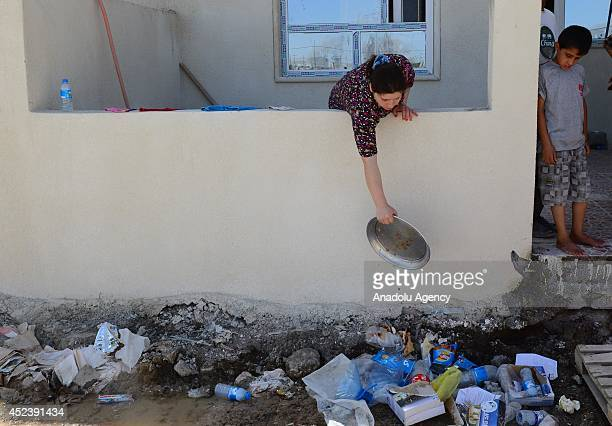 An Iraqi woman puts garbage in front of a building as Iraqi Christians family fleeing violence in the northern city of Mosul arrive at Arbil on July...