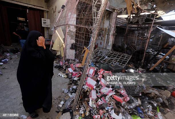 An Iraqi woman reacts as she stands amid the debris in the aftermath of a massive suicide car bomb attack carried out by the Islamic State group in...