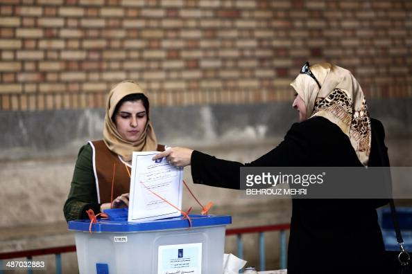 An Iraqi woman residing in Iran casts her ballot for Iraq's parliamentary elections at a polling station in southern Tehran on April 27 2014 Iraqi...