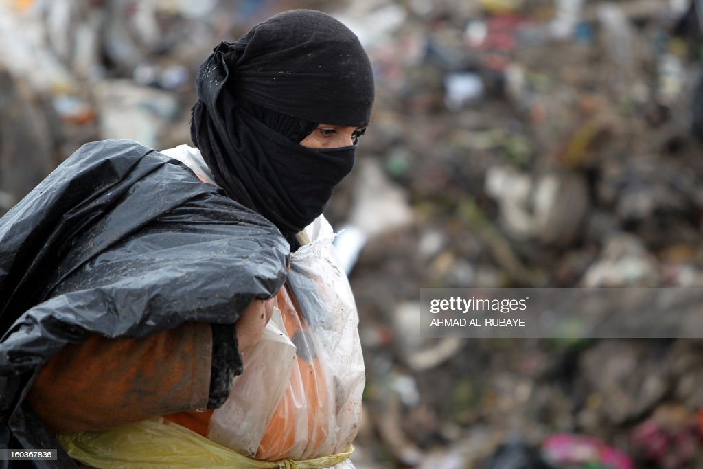 An Iraqi woman searches for plastic bottles in a garbage dump on the outskirts of Baghdad's impoverished district of Sadr City, January 30, 2013. Around a quarter of Iraq's population are estimated by the country's Planning Ministry to live in poverty, and many survive in vast refuge dumps where they search for subsistence, either via using disposed goods or finding items that can be handed to recycling plants for money. AFP PHOTO/AHMAD AL-RUBAYE