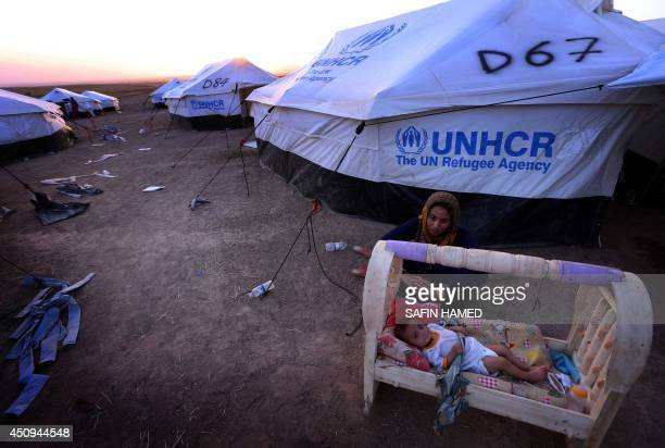 An Iraqi woman sits next to her child in northern Iraq on June 20 at a temporary camp in Aski kalak 40 kms west of the Kurdish autonomous region's...