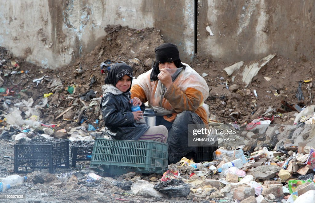An Iraqi woman sits with her daughter in a garbage dump on the outskirts of Baghdad's impoverished district of Sadr City, January 30, 2013. Around a quarter of Iraq's population are estimated by the country's Planning Ministry to live in poverty, and many survive in vast refuge dumps where they search for subsistence, either via using disposed goods or finding items that can be handed to recycling plants for money.