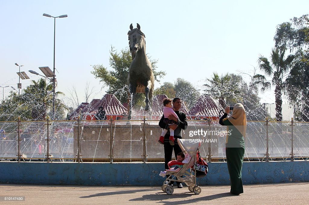 An Iraqi woman takes photos of her family members on Valentine's day at Baghdad's Al-Zawraa Park on February 14, 2016. / AFP / Sabah ARAR