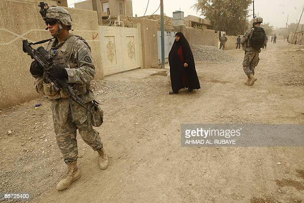An Iraqi woman walks along a street in a residential neighborhood as US soldiers and Iraqi police carry out their last patrol in Khan Bani Saad some...