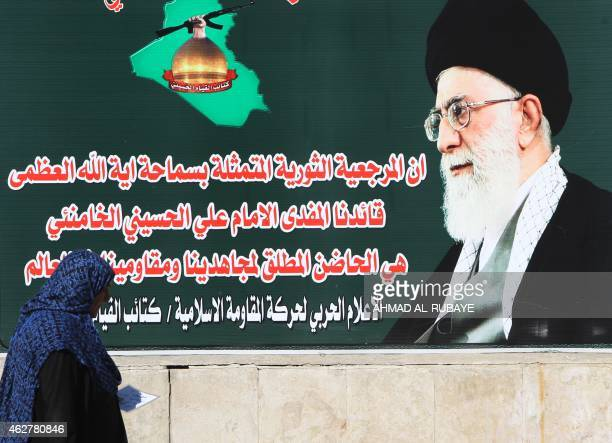 An Iraqi woman walks past a giant poster showing Iran's supreme leader Ayatollah Ali Khamenei in Tahrir Square in central Baghdad on February 05 2015...