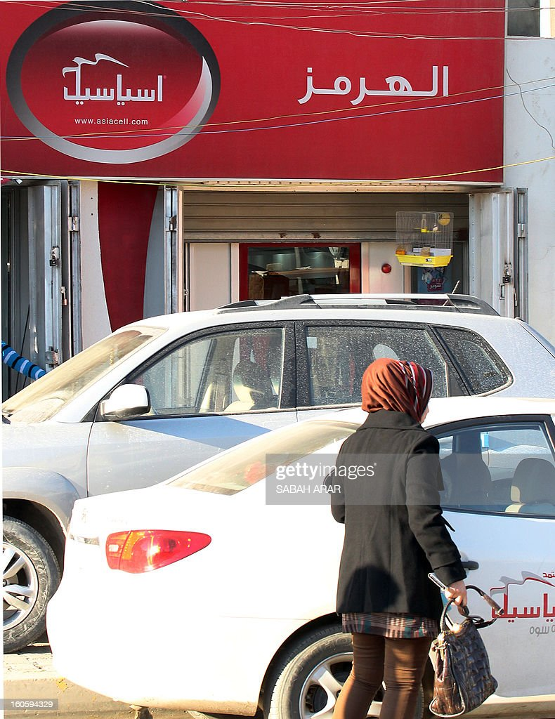 An Iraqi woman walks past an advert for the Asiacell, a mobile phone provider, in Baghdad on February 3, 2013, as Iraq's second largest mobile operator debuted on the Baghdad bourse in the country's first major stock flotation and after pressure from the media regulator for it to be publicly listed. Asiacell, which is majority-owned by Qatar Telecom, offered 67.503 billion shares, representing 25 percent of the total share capital, according to a statement on the Iraq Stock Exchange (ISX).
