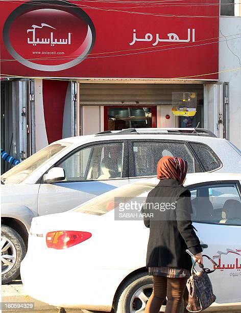 An Iraqi woman walks past an advert for the Asiacell a mobile phone provider in Baghdad on February 3 as Iraq's second largest mobile operator...