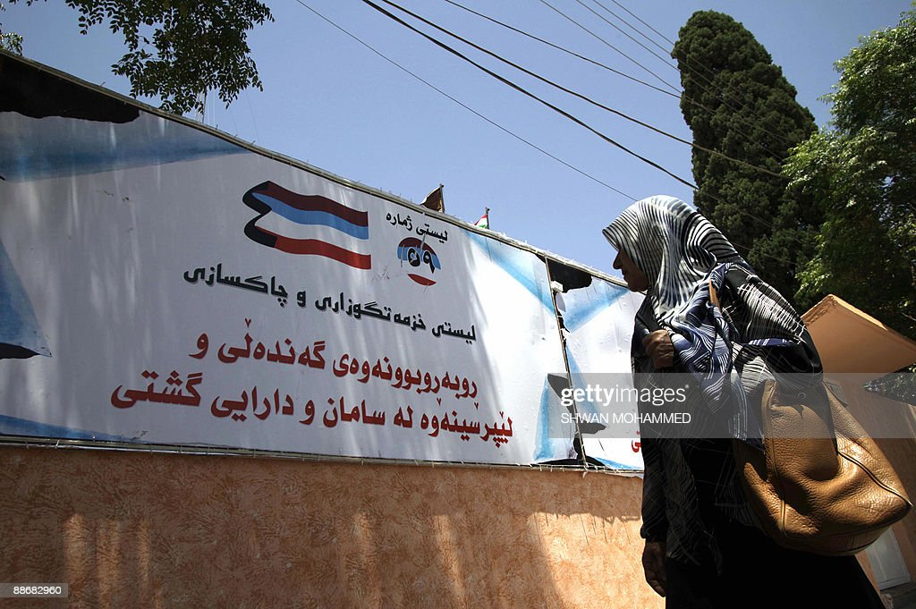 An Iraqi woman walks past an election campaign banner plastered to a wall in the northern city of Sulaimaniyah 330 kms from Baghdad on June 25 2009...
