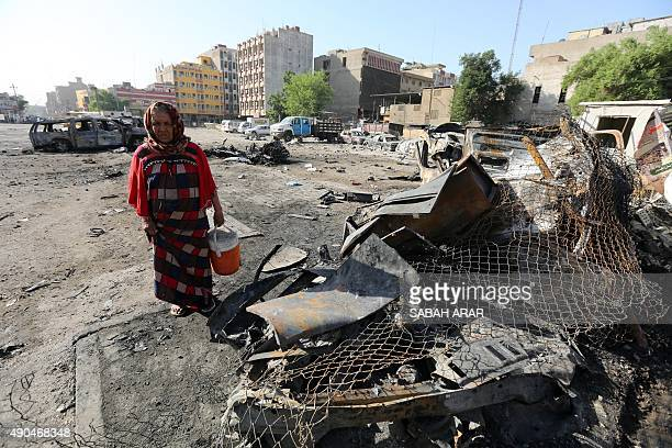 An Iraqi woman walks past burnt cars at the site of a car bomb explosion near a liquor store in central Baghdad's Battaween area early on September...