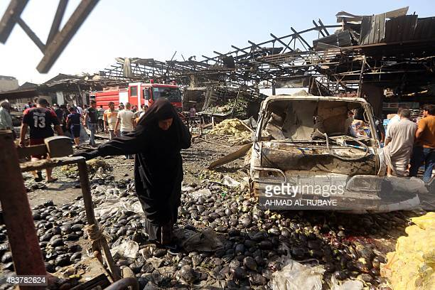 An Iraqi woman walks past debris as men look at the damage following a bomb explosion that targeted a market in Baghdad's northern Shiite district of...