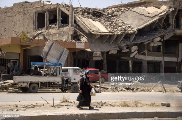 An Iraqi woman walks past destroyed buildings in west Mosul on July 12 2017 after the government declared it had driven the Islamic State group...