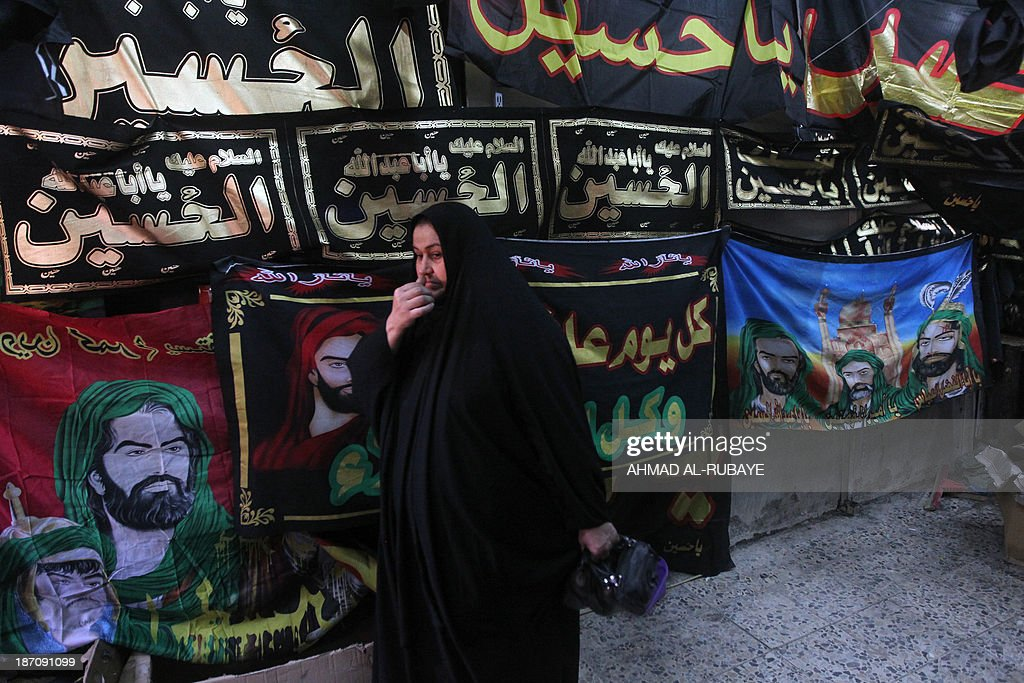 An Iraqi woman walks past religious flags in a Baghdad Shiite suburb ahead of preparation for Ashura which will take place on November 14, 2013 as Shiite Muslims prepare to commemorate the seventh century killing of Imam Hussein next week.